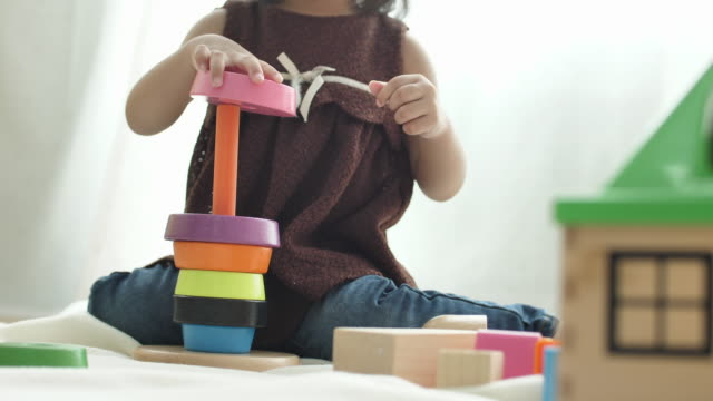 Close up Child playing with toy blocks at home