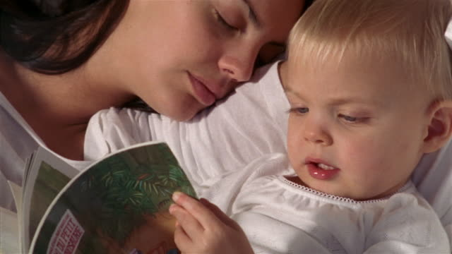 close up child reading storybook in bed as mother sleeps next to him - tired stock videos & royalty-free footage
