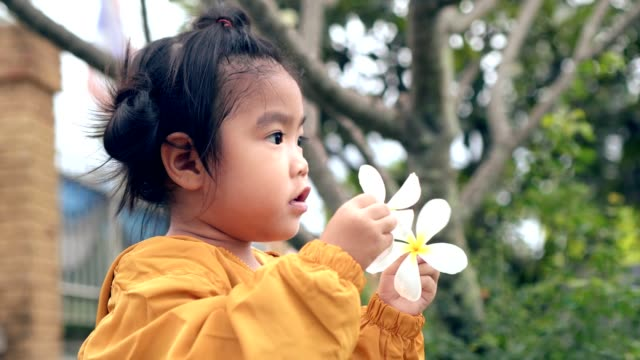 close up child-girls hold white flower and walking