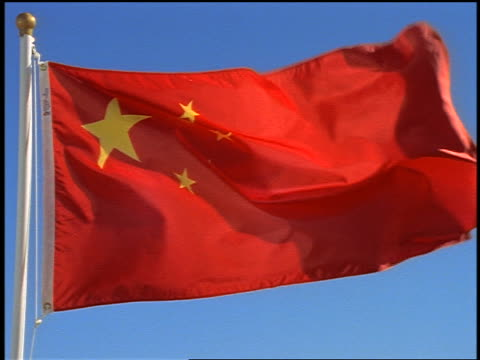 close up pan chinese flag blowing in wind / blue sky in background - chinese flag stock videos & royalty-free footage