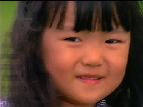 stockvideo's en b-roll-footage met close up chinese girl with wind blowing hair looking at camera outdoors - alleen meisjes