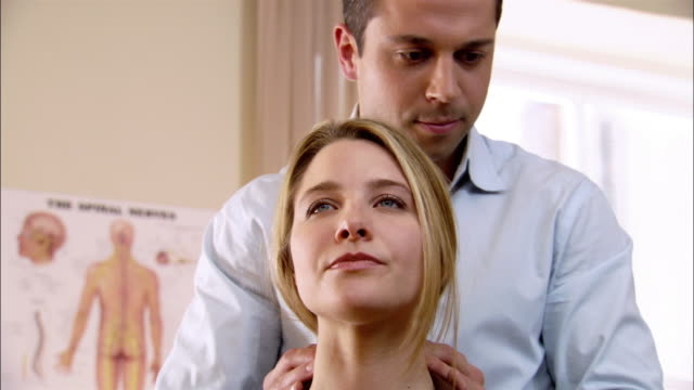 close up chiropractor adjusting woman's neck - physical therapy stock videos & royalty-free footage