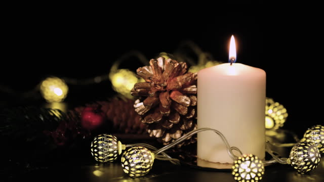 close up christmas candle with pine cone,fir,mistletoe and vintage light string on black table at night - pinecone stock videos & royalty-free footage