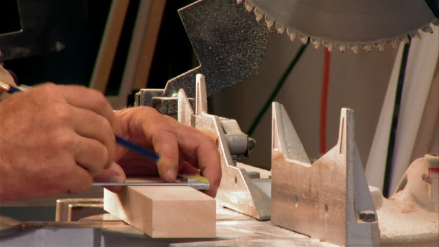 Close up circular saw blade/ tilt down hands writing on board/ saw cutting wood/ Santa Fe, New Mexico