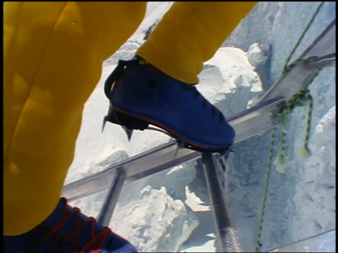close up climber's spiked boots on ladder / tilt up to low angle of male climber on ladder up wall of ice / everest - ladder stock videos & royalty-free footage