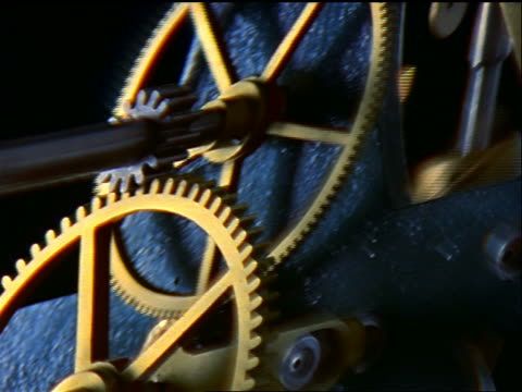 stretching + twisting close up clock gears moving - inquadratura dall'alto di un tavolo video stock e b–roll