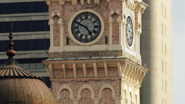 close up clock tower/ zoom out wide shot fast motion traffic passing in front of sultan abdul samad building/ kuala lumpur - clock tower stock videos & royalty-free footage