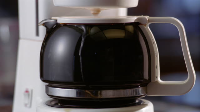 close up coffee dripping from coffee maker into full carafe / coffee overflowing carafe - overflowing stock videos & royalty-free footage
