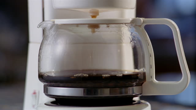 close up coffee dripping from coffee maker into pot - filling stock videos & royalty-free footage