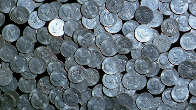 Close up coins falling into pile
