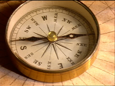 close up compass with moving needle on top of old map