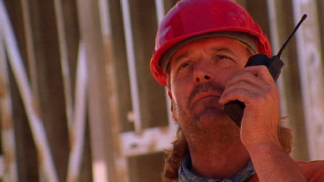 close up construction worker talking on walkie talkie + pointing off camera / dust in background - one mid adult man only stock videos & royalty-free footage