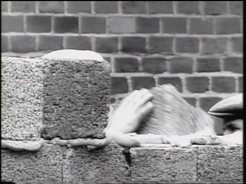 close up construction worker's hands laying concrete blocks for berlin wall / cold war / germany - ziegel stock-videos und b-roll-filmmaterial