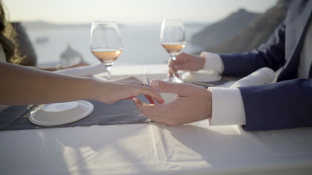 close up couple holding hands during romantic dinner