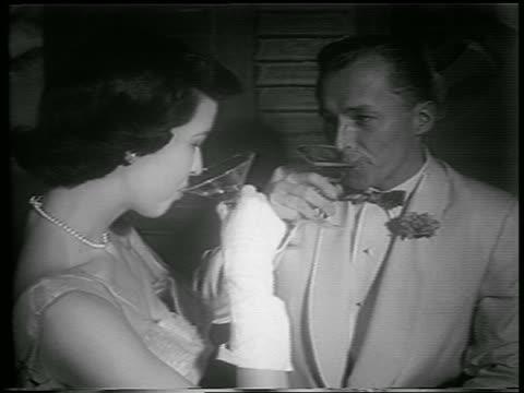 b/w 1953 close up couple in formalwear drinking champagne + talking / newsreel - paar mittleren alters stock-videos und b-roll-filmmaterial