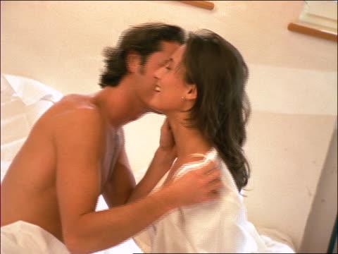 close up couple in white bedroom kissing + undressing - heterosexuelles paar stock-videos und b-roll-filmmaterial