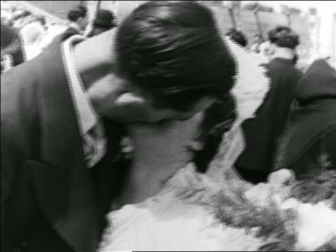 vídeos de stock, filmes e b-roll de b/w 1939 close up couple kissing after getting marrried in ceremony in stadium / montreal / newsreel - casal de idade mediana