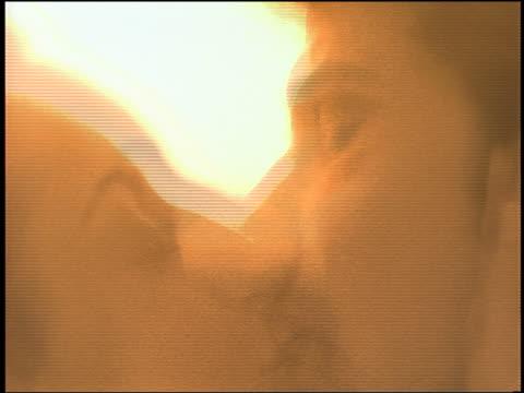 vídeos de stock, filmes e b-roll de close up couple kissing / pan to eiffel tower seen thru window - imagem tonalizada