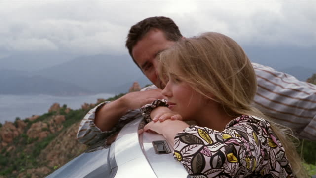 close up couple looking out over windshield of parked convertible/ pan view of mountains and water/ corsica - 年の差カップル点の映像素材/bロール