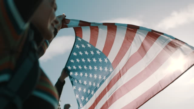 close up, couple of hikers raising american flag up in the air - american flag stock videos and b-roll footage