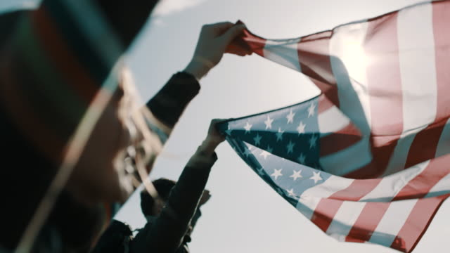 close up, couple of hikers raising american flag up in the air - stati uniti d'america video stock e b–roll