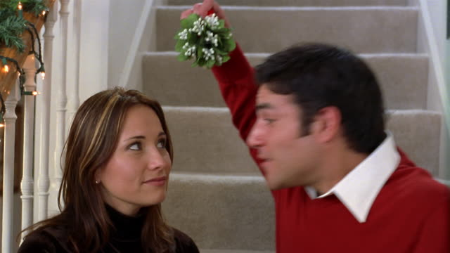 Close up couple sitting on stairs / man holding mistletoe and kissing woman / woman kissing back / Texas