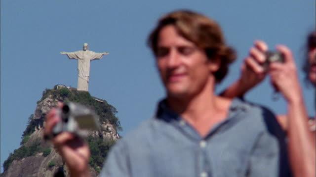 vídeos y material grabado en eventos de stock de close up couple taking pictures at corcovado mountain w/statue of christ in background /  rio de janeiro - jesucristo