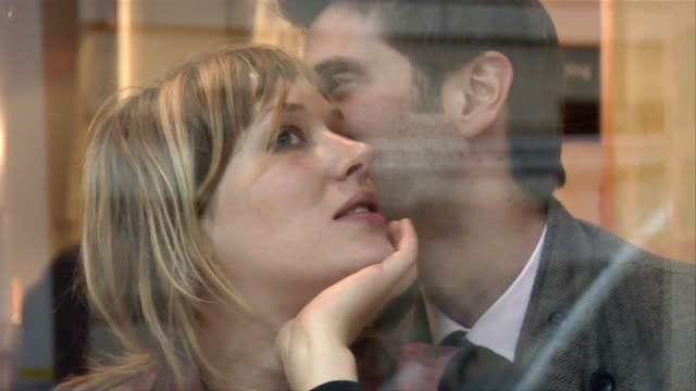 vídeos y material grabado en eventos de stock de close up couple talking and kissing through shop window/ london - mano en la barbilla