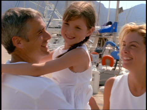 vídeos y material grabado en eventos de stock de close up couple walk + cuddle along dock in marina with small girl in man's arms / corsica - 1990