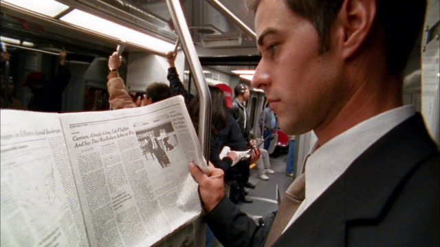 vídeos de stock e filmes b-roll de close up crane shot commuter reading newspaper on subway - jornal
