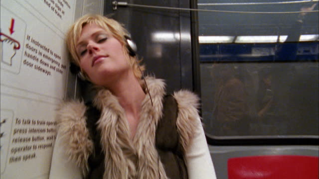 close up crane shot young blonde woman listening to mp3 player on subway / opening eyes / smiling - underground train stock videos & royalty-free footage