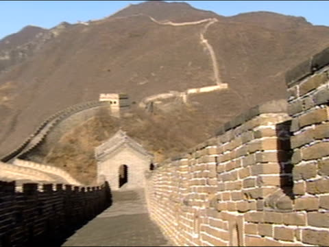Close up crenellation in brick wall / long shot pan of Great Wall of China with mountains in background