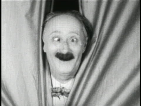 b/w 1928 close up cross-eyed man (ben turpin) looking out of curtains / short - 1928 stock-videos und b-roll-filmmaterial