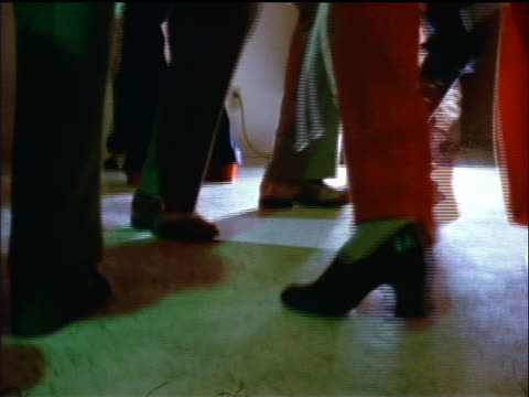 1974 close up crowd of feet dancing at party indoors / documentary - 1974 bildbanksvideor och videomaterial från bakom kulisserna