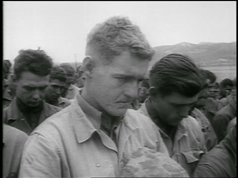 B/W 1950 close up crowd of grieving soldiers bowing heads in prayer / Korean War / newsreel