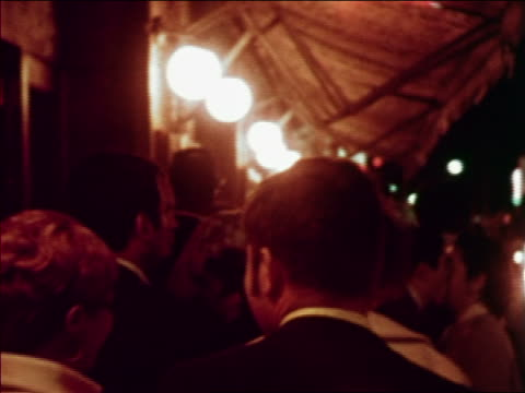 1969 close up crowd of people standing under awning on city sidewalk outdoors / greenwich village, nyc - greenwich village stock videos & royalty-free footage