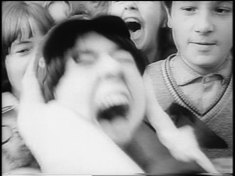 b/w 1965 close up crowd of screaming teen beatles fans outdoors / london / newsreel - klassischer rock and roll stock-videos und b-roll-filmmaterial