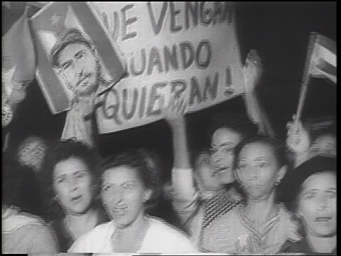 b/w 1962 close up crowd of women hold poster picture of castro at demonstration / cuban missile crisis - cuban missile crisis stock videos & royalty-free footage
