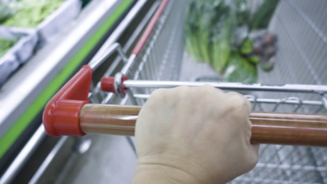 close up customer hand moving shopping cart in gerocery store - trolley stock videos and b-roll footage