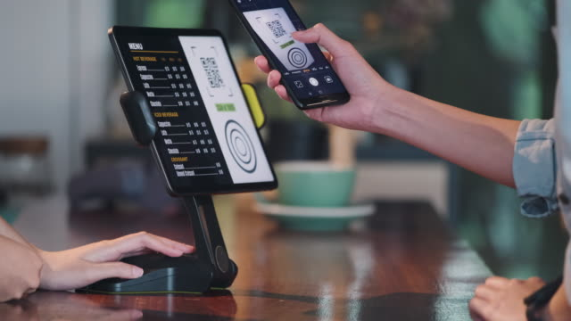 close up customer use mobile phone pay contactless with tablet at counter bar in cafe.small business start up.customer service concept - digital display stock videos & royalty-free footage