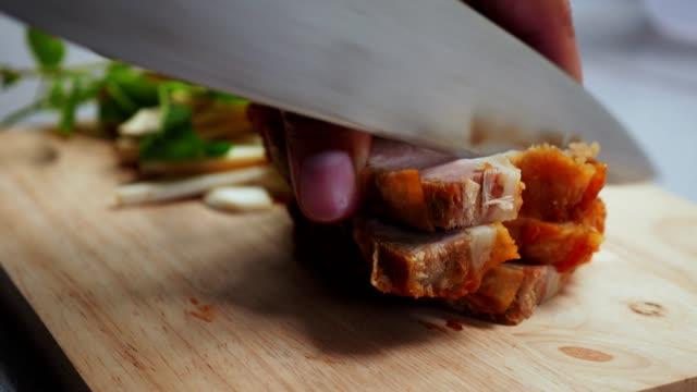 vídeos de stock e filmes b-roll de close up cutting crispy pork on wooden cutting board - porco