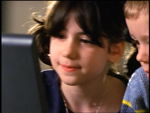 close up dark-haired young girl with pigtails + blonde young boy looking at laptop computer screen