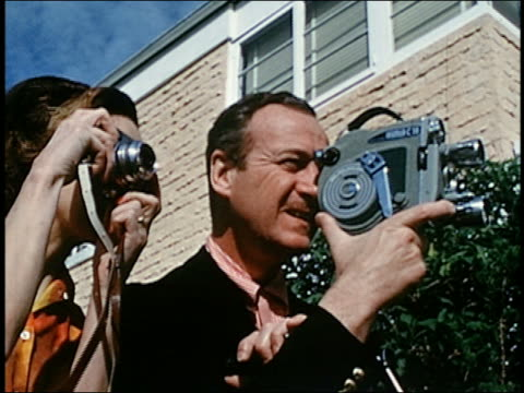 close up david niven holding and looking through home movie cam / woman standing next to him w/cam - 40 44 anni video stock e b–roll