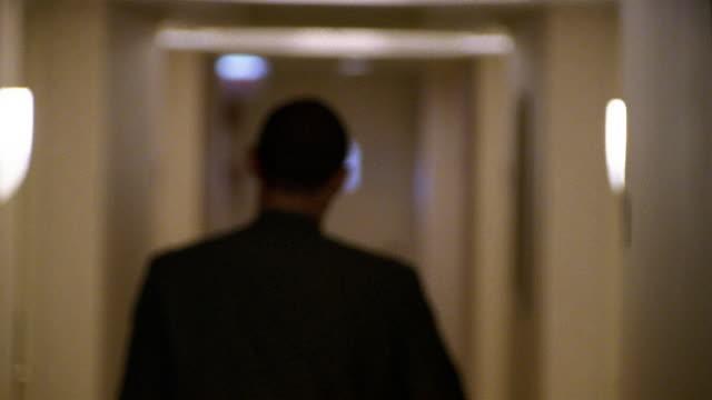 vidéos et rushes de close up defocus man walking down hallway in hotel / opening room door - porte entrée