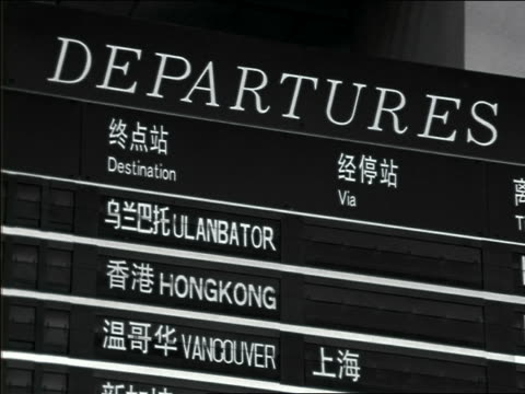close up departure board in asian airport - segnale informativo video stock e b–roll