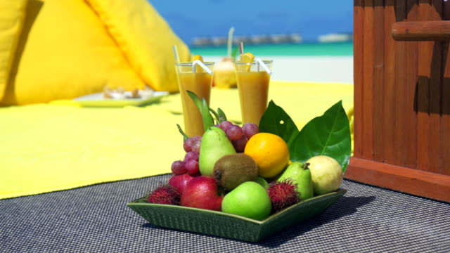 Close up detail of a fruit plate at a picnic on a tropical island beach.