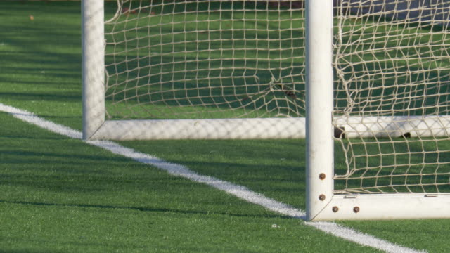 close up detail of a soccer goal and net football on a turf grass field. - slow motion - netting stock videos & royalty-free footage
