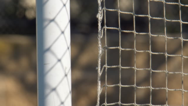 close up detail of a soccer goal and net football on a turf grass field. - slow motion - カーテン レース点の映像素材/bロール