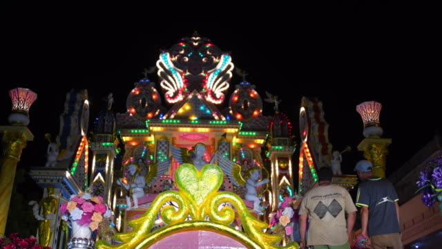 close up detail of the float belonging to the 'chivos' district. it is partially illuminated and workers are giving a final touch before it is shown... - 社会史点の映像素材/bロール