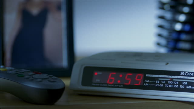Close up digital alarm clock at 6:59 AM / time changing to 7 AM / hand hitting snooze or turning off alarm